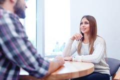 Ett älska par och att sitta i ett kafé, tala och seende lovingly de Arkivfoton