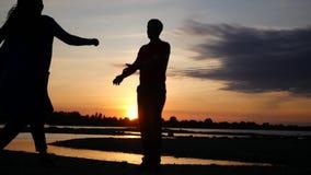 Ett älska par på ett datum vid floden med en solnedgång, en man som cirklar en kvinna i hans armar HD 1920x1080 långsam rörelse stock video