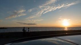 Ett älska par på kusten av det Kiev havet, i förgrunden en soltak för Ñ-ar Royaltyfri Bild