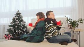 Ett älska par sitter tillbaka för att dra tillbaka och dricker varmt kaffe julhelgdagsaftongåvor semestrar många prydnadar Varm a lager videofilmer