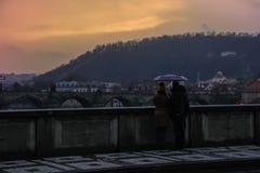 Ett älska par som står under ett paraply med en sikt av Charles Bridge i regnet på solnedgången fotografering för bildbyråer