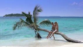Ett älska par som tycker om semester på en tropisk strand långsam rörelse arkivfilmer