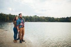 Ett älska par står på banken av en bergflod som omfamnar royaltyfri foto