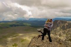 Ett älska par står på berget som kramar mot royaltyfri fotografi