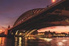 Ett älska par står på en bro över floden av aftonstaden arkivfoton