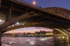 Ett älska par står på en bro över floden av aftonstaden fotografering för bildbyråer