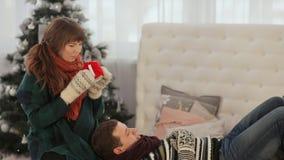 Ett älska par vilar på sängen och dricker varmt te Varm julafton lager videofilmer