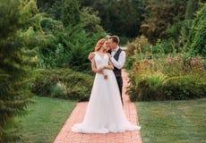 Ett älskvärt ungt par, en brud i en lång ljus vit bröllopsklänning och en brudgum i en ursnygg grön trädgård en man fotografering för bildbyråer