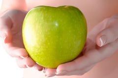 Ett äpple i händerna av en flicka Royaltyfri Foto