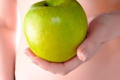 Ett äpple i händerna av en flicka Arkivbilder