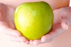 Ett äpple i händerna av en flicka Royaltyfria Bilder