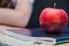ett äpple ligger på en anteckningsbok för ett mellanmål på ett avbrott royaltyfri bild