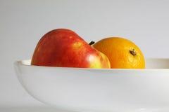 Ett äpple och en apelsin Fotografering för Bildbyråer