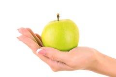 Ett äpple på den isolerade handen Arkivbild