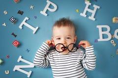Ett årigt barn som ligger med anblickar och bokstäver Royaltyfri Foto