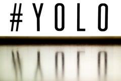 Ett övre bräde för ljus som visar uttrycket YOLO royaltyfri bild