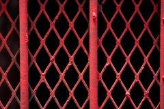 Ett abstrakt begreppskott av fint rött målat trådgaller på gallerförsedda wi Royaltyfri Foto