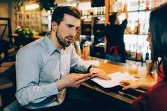 Ett affärsmöte av två personer i en stång Mannen förklarar något till kvinnan Hon lyssnar till honom som mycket är exakt royaltyfri fotografi