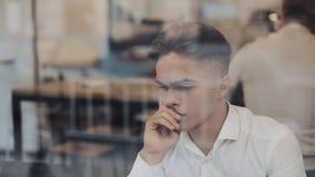 Ett allvarligt ungt affärsmansammanträde på en tabell i ett kafé som arbetar på en bärbar dator Frilans kommunikation, IT som är  arkivfilmer