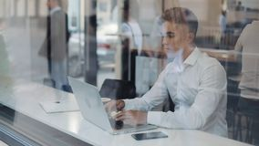 Ett allvarligt ungt affärsmansammanträde på en tabell i ett kafé som arbetar på en bärbar dator Frilans kommunikation, IT som är  stock video