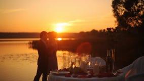 Ett amoröst par är kyssande på solnedgången