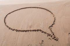 Ett anförande eller en funderarebubbla som dras ut på en sandig strand pink scallop seashell Royaltyfri Foto