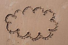 Ett anförandemoln eller en funderarebubbla som dras ut på en sandig strand pink scallop seashell Arkivfoto