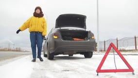 Ett anseende för ung kvinna vid en bruten bil Fånga en bil för hjälp Ett nöd- tecken arkivfoto