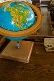 Ett antikt världsjordklot på ett skrivbord arkivbilder