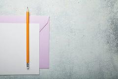 Ett ark av papper, ett rosa kuvert och en blyertspenna Förälskelsevalentin på en vit tappningbakgrund kopiera avst?nd royaltyfri foto