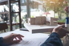 Ett arkitektarbete och innehav som en arkitektur modellerar med shoppar teckningspapper Arkivfoto