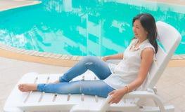 Ett asiatiskt kvinnaanseende bredvid en simbassäng royaltyfri bild