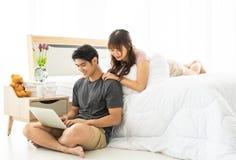 Ett asiatiskt par använder bärbara datorn i sovrum arkivfoto