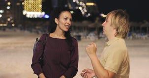 Ett attraktivt par som pratar på en stadsstrand i aftonen lager videofilmer