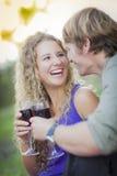 Ett attraktivt par som tycker om ett exponeringsglas av vin i parkera Fotografering för Bildbyråer