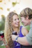 Ett attraktivt par som tycker om ett exponeringsglas av vin i parkera Arkivfoton