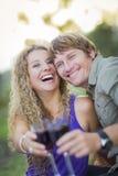 Ett attraktivt par som tycker om ett exponeringsglas av vin i parkera Royaltyfria Bilder