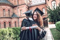 Ett av de mest lyckliga ögonblicken av mitt liv Lyckliga kandidater står nära universitet och kramar sig arkivbild