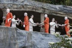 Ett avsnitt av den guld- templet som visar statyer för buddistisk munk som mottar offerings Royaltyfria Bilder
