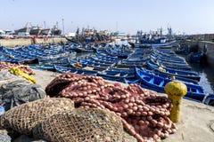 Ett avsnitt av den upptagna fiskehamnen på Essaouira i Marocko visningfisknät, små fartyg och trålare Arkivfoto