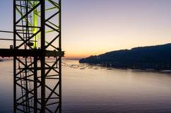 Ett avsnitt av en tornkran med havet som bakgrund under solnedgången fotografering för bildbyråer