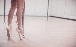 Ett balettdansöranseende i Pointe nära pol i den tomma studion med trägolvet Närbild Royaltyfria Bilder