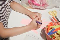 Ett barn drar med kulöra blyertspennor på papperet gömma i handflatan arkivbilder