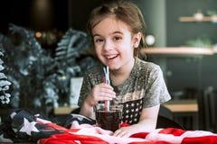 Ett barn dricker en drink från ett sugrör arkivbild