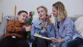 Ett barn ger blommor och mamman arkivfilmer