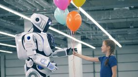 Ett barn ger upp ballonger till en vit robot, slut stock video