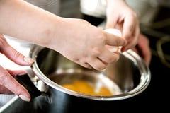 Ett barn hjälper mammakockfrukosten och bryter ägg in i en kastrull royaltyfri bild