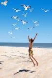 Ett barn hoppar in mot flygseagulls Royaltyfria Bilder