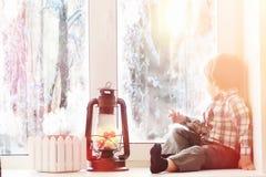 Ett barn i det nya året ser ut fönstret Barn är waitien Royaltyfri Foto