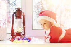 Ett barn i det nya året ser ut fönstret Barn är waitien arkivfoton